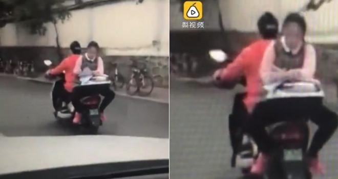 Nữ sinh tranh thủ làm bài tập khi ngồi ngược sau xe máy