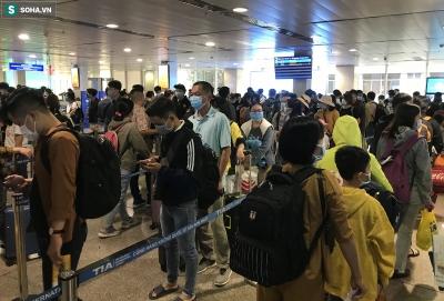 Ảnh: Người dân mặc áo mưa, đồ bảo hộ kín mít tại sân bay Tân Sơn Nhất chờ về quê đón Tết